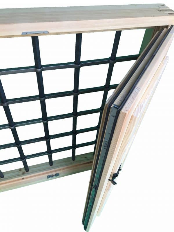 Imagen de una ventana de madera con reja. Destaca el detalle de cierre hermético y reja.