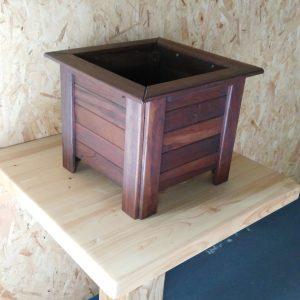Macetero de madera oscura con forma cuadrada. Su diseño de cuatro patas hace que el interior quede desplazado del suelo.